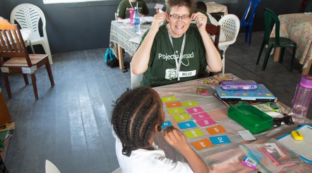 Niña aprende el abecedario durante nuestro voluntariado para enseñar inglés en Belice.